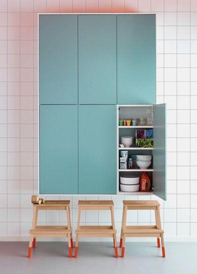 Farbenfrohes Stauraummöbel mit stylischen Hockern. Die bunten Füße der Hocker stehen im aufregenden Kontrast zum Wandschrank.