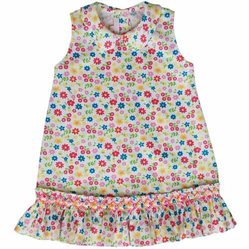 This is such a beautiful A-line Hania dress, full of flowers and fun! A Fuchsia, Light Pink, blue, and yellow floral pattern covers the entire white dress, which is hand smocked along a ruffled hemlin