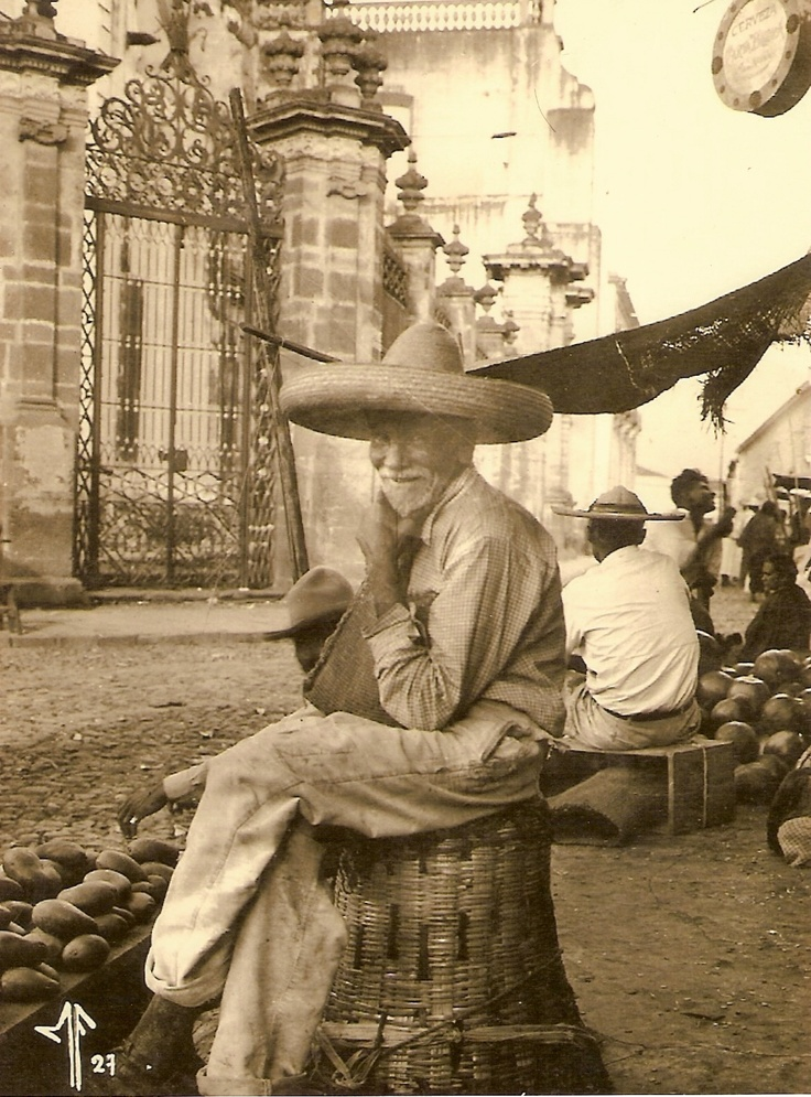 Man selling produce in front of the Cathedral Zamora, Michoacan 1927