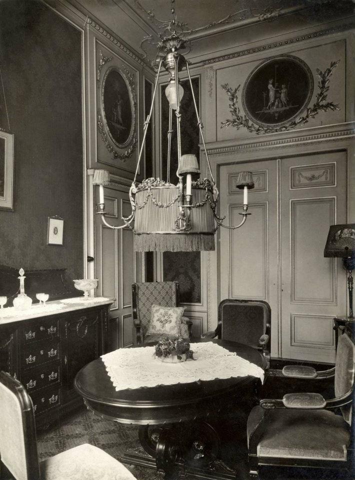 1913 Woninginrichting. Eetkamer Louis XVI in Meubelzaak t Woonhuys dressoir met marmeren blad en een bijzondere hanglamp