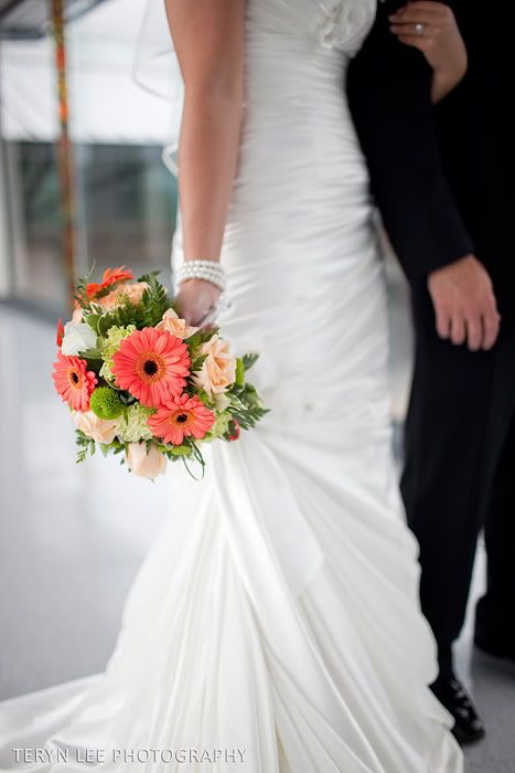 Coral gerberas, peach roses, white roses, green poms, touch of yellow mini gerbera.