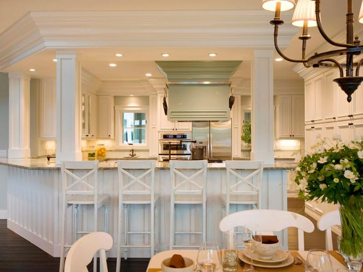 With white chairs, cabinets and columns, this kitchen has a clean country feel. The peninsula seats eight people, and the custom-designed light green stove hood adds an interesting element to the space. Design by Shane Inman