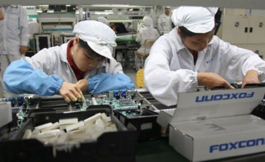 This pin shows the workers of foxconn. They are making apple products in a sweatshop.