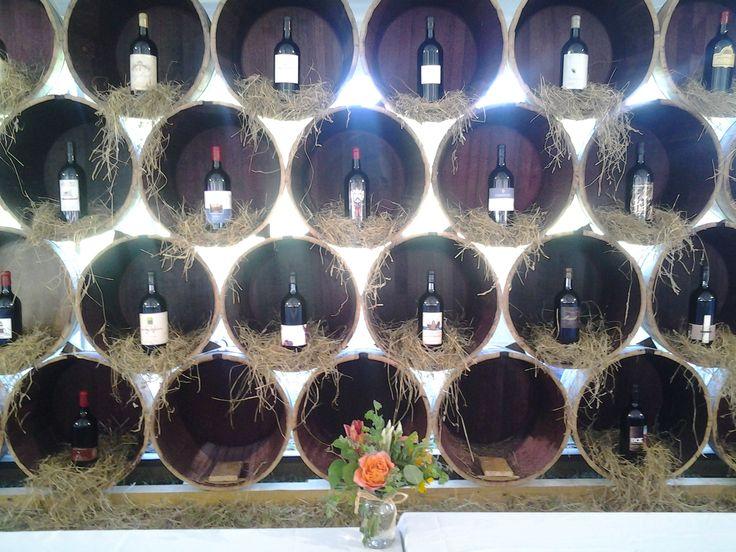 Jeroboam wine bottle display for silent auction. The bottles are inside of wine barrels.