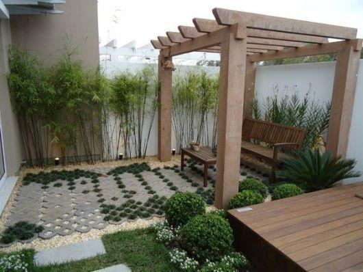 Quintal com pergolado. Com pouco espaço, a ideia foi aproveitar para fazer a jardinagem beirando o muro com bambu decorativo, e ainda criar um pergolado com banco para ter uma área de descanso.
