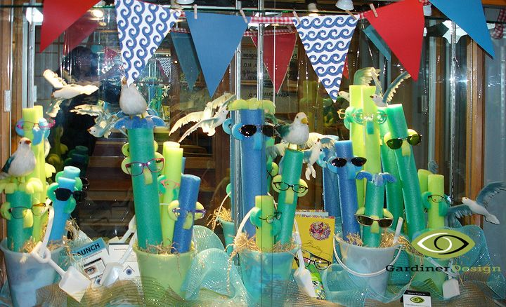 "Premier Optical summer Window Displays ummer Window Display 2015 (Details)  ""Use your Noodle, wear UV Protected Sunglasses! For this window I cut up, then reconstructed, water noodles to create characters who stand up in similarly colored pails with shovels."