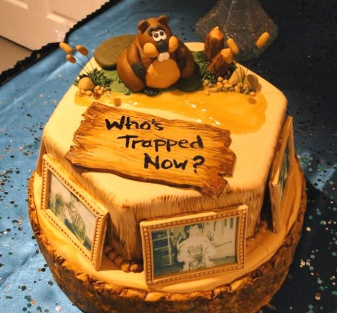 """Trapper's Groom Cake - I made this for my nephew's wedding. He's an avid trapper and hunter. All is edible except for the stalks of the cattails. It was a 16"""" 2 layer round (yellow cake w/ lemon filling) topped by a 12"""" 2 layer hex (chocolate cake w/ Bavarian cream filling). The photos of my nephew were edible images with gumpaste frames and the bark on the bottom layer was made using a silicone mold that I made from a tree from our farm where he hunts."""