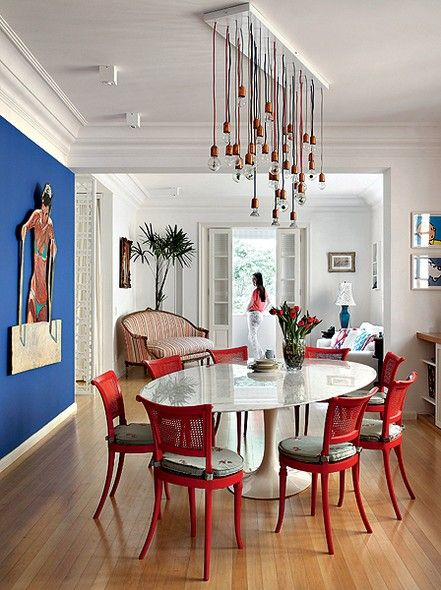 Como a moradora Aniela Jordan adora cores, tons intensos passeiam à vontade pelos espaços. Uma das paredes foi pintada de azul para lembrar uma piscina e sugerir que dela sai uma mulher. As cadeiras de família ganharam leveza com a pintura vermelha