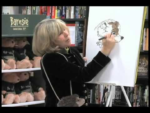 Author Jan Brett explains how she drew the bear from The Mitten to a group of students.