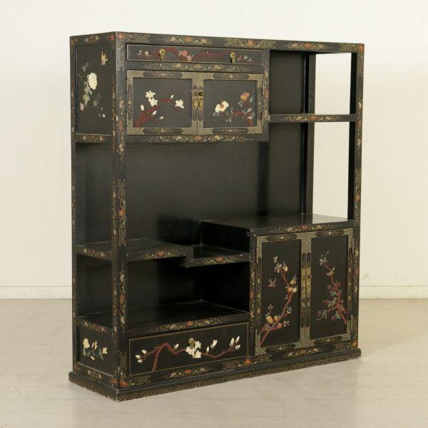Presenta due cassetti, vani a giorno e quattro ante. Impreziosita da decorazioni chinoiserie in policromia e pietre dure in bassorilievo.