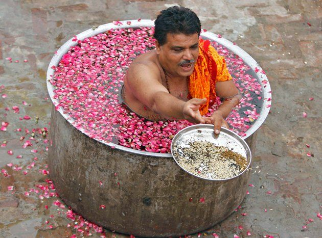 """A Hindu priest sits in a cauldron of water and makes offerings to a fire while performing the """"Parjanya Varun Yagam"""", a special prayer for rain, in the western Indian city of Ahmedabad July 1, 2012. Hindus believe the prayer appeases the god Varuna, who favours them with rain if the ritual is performed. REUTERS/Amit Dave"""