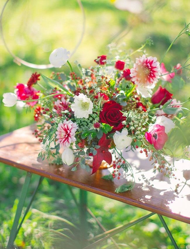 red centerpiece with anemones, scabiosas, and roses