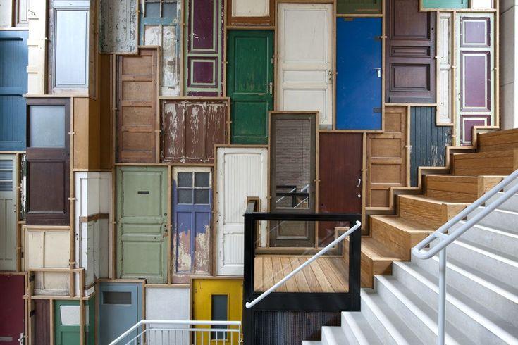 Een wand bij een van de entree's van het Borneohof in Amsterdam oost, met een kunstwerk van Piet Hein Eek dat volledig bestaat uit deuren.  Waar hebben we dat meer gezien? Architectenbureau Geusebroek Stefanova is de architect van het gehele woon- &...