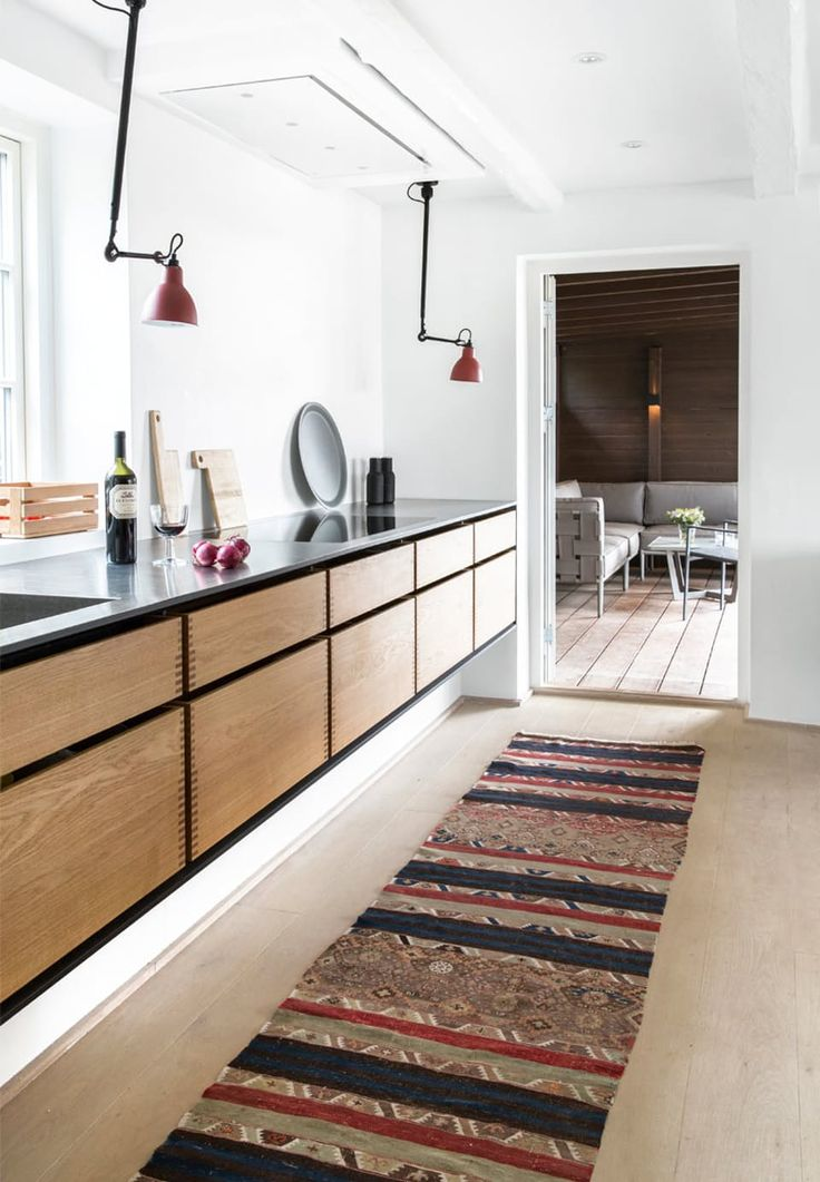 Warm kitchen made of oiled oak, black linoleum and brushed steel by Garde Hvalsøe.