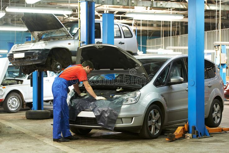 Auto mechanic at work. One young auto mechanic examining