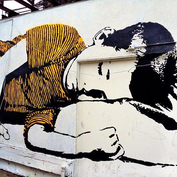Boy sleeping on the side of a building. Street art love.