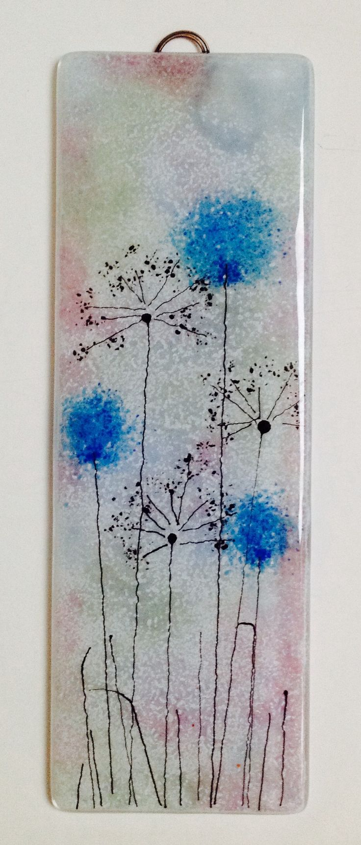 Fused glass panel in pale blue and pink with blue frit flowers and black seed head silhouettes. Email : info@firedcreations.co.uk