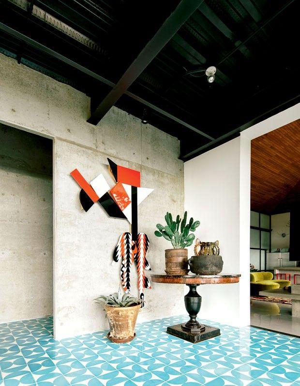 Hall de entrada com obra de Assume Vivid Astro Focus na parede de concreto, vasos de cerâmica maia e piso de ladrilho cerâmico azul de Dario Escobar