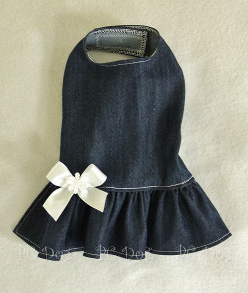 - Denim dress - Dark denim dress with a white bow and daisy center - Shown over a white lace turtleneck, but does NOT include the shirt - It easily attaches with adjustable velcro neck and belly strap
