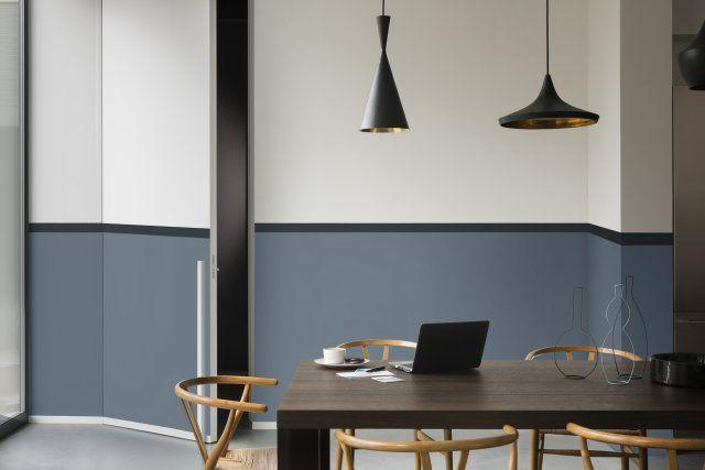 Un soubassement bleu gris pour un joli trompe-l'oeil.   Envie de donner un peu de relief à vos murs ? Optez pour le mur bi-colore ! Ici le soubassement du mur s'habille d'un bleu gris et la partie supérieure de celui-ci affiche un blanc cassé pour un rendu inattendu.