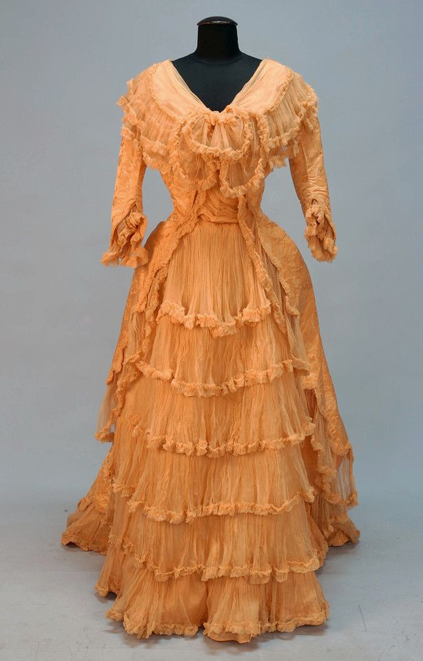 """FRENCH SILK EVENING GOWN, 1888. Gold damask in an abstract floral pattern, One-piece with boned bodice having 3/4 sleeve trimmed in gold chiffon ruffles, trained skirt with cutaway front over front panel with rows of chiffon ruffles, Petersham stamped """"A La Grande Maison de Blanc Arthur Bigot Tours""""."""