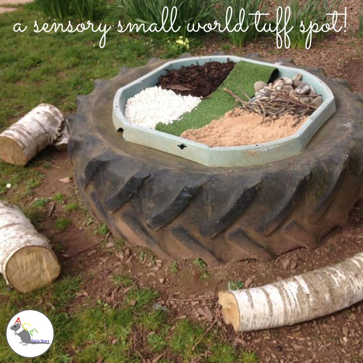A sensory small-world tuff spot! Using bark, fake grass, gravel, sand, sticks and cobbles! #eyfs #earlyyears #tuffspot #outdoors #eyfsoutdoors #aceearlyyears