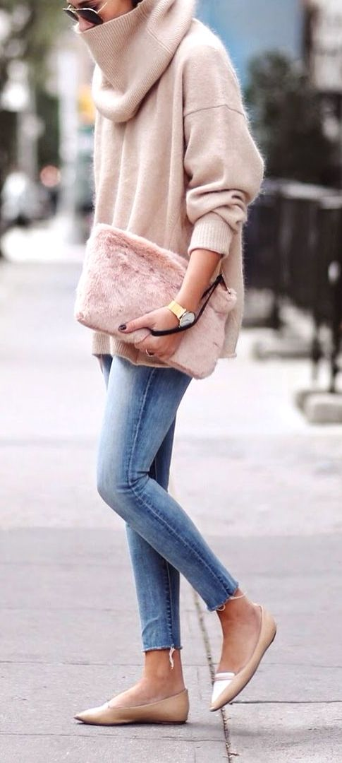 Oversized blush pink turtleneck sweater over skinny jeans and pointy toed flat shoes