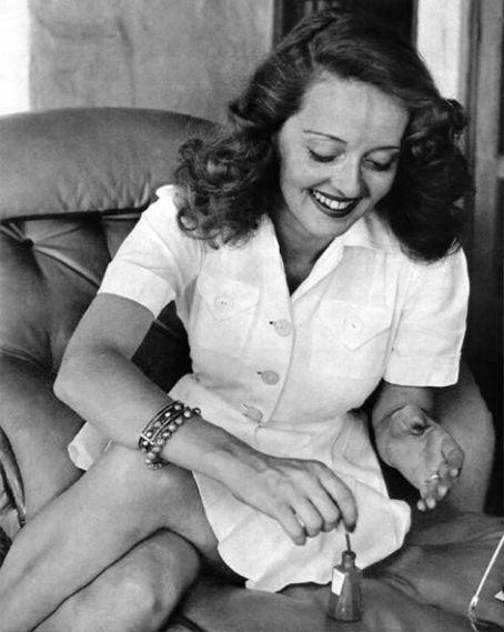 Bette Davis, white buttoned dress, curly hair, bracelets