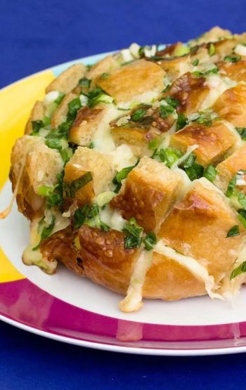 Pão Italiano recheado de queijo, manteiga temperada com alho e cebolinha