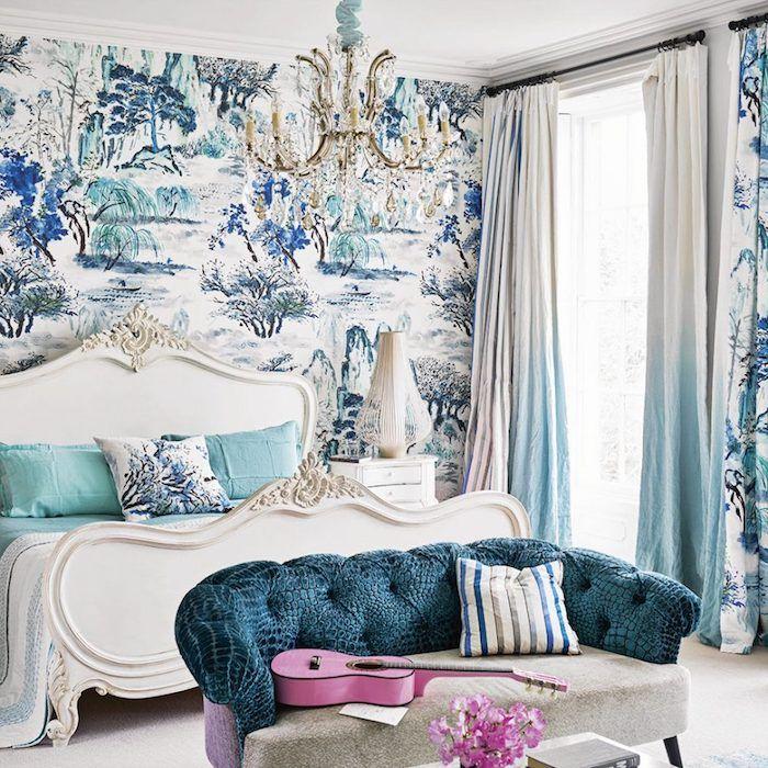 papier peint baroque, exemple de revetement mural, motif nature, arbres, arbustes bleu et vert sur un fond blanc, lit baroque, canapé et lustre baroque, guitare rose