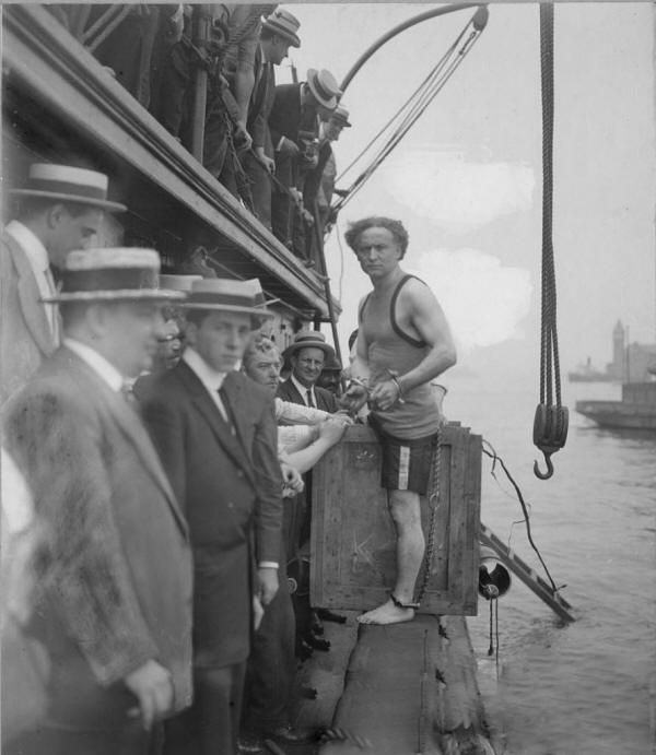 Harry Houdini in 1912 in chains, about to be lowered into the East River.