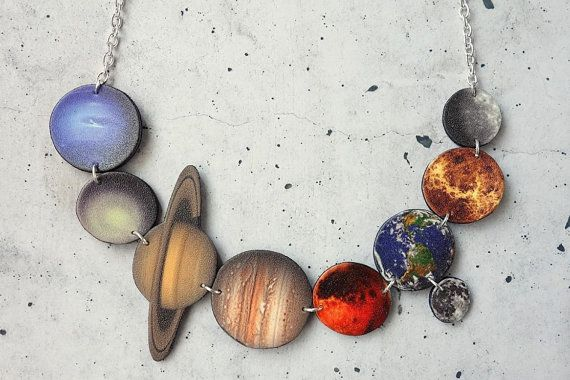 This funky necklace features all of the planets in our solar system, as captured by NASA, in order of distance from the sun. These are Mercury, Venus, Earth, Mars, Jupiter, Saturn, Uranus and Neptune. Even our moon makes an appearance! Each planet is made out of shrink plastic, carefully cut and coated with a few layers of protective varnish before being strung together.  Note that the silver plated chain includes a clasp at the back. The backs of the pieces are coloured black, as is seen in…