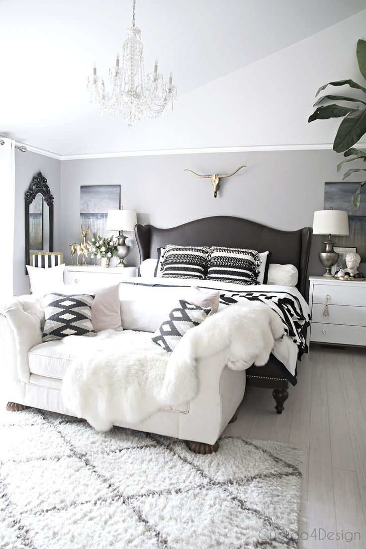 beautiful serene bedroom with leather wingback bed | brass longhorn skull | cathedral ceilings | crystal chandelier | blush and black and white accents