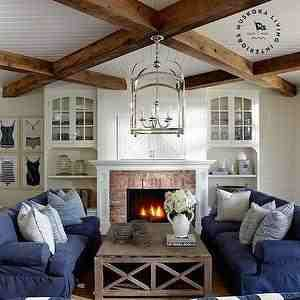 lake rousseau muskoka ontario coastal style lake cottage living room with wooden beams over white beadboard slipcovered navy sofas and tv concealed