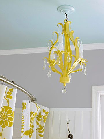After: Colorful Hues A home center chandelier, originally in an aged silver finish, received several coats of yellow paint. Sky blue paint covers the ceiling, an unexpected touch, and complements the baths sunny accents.