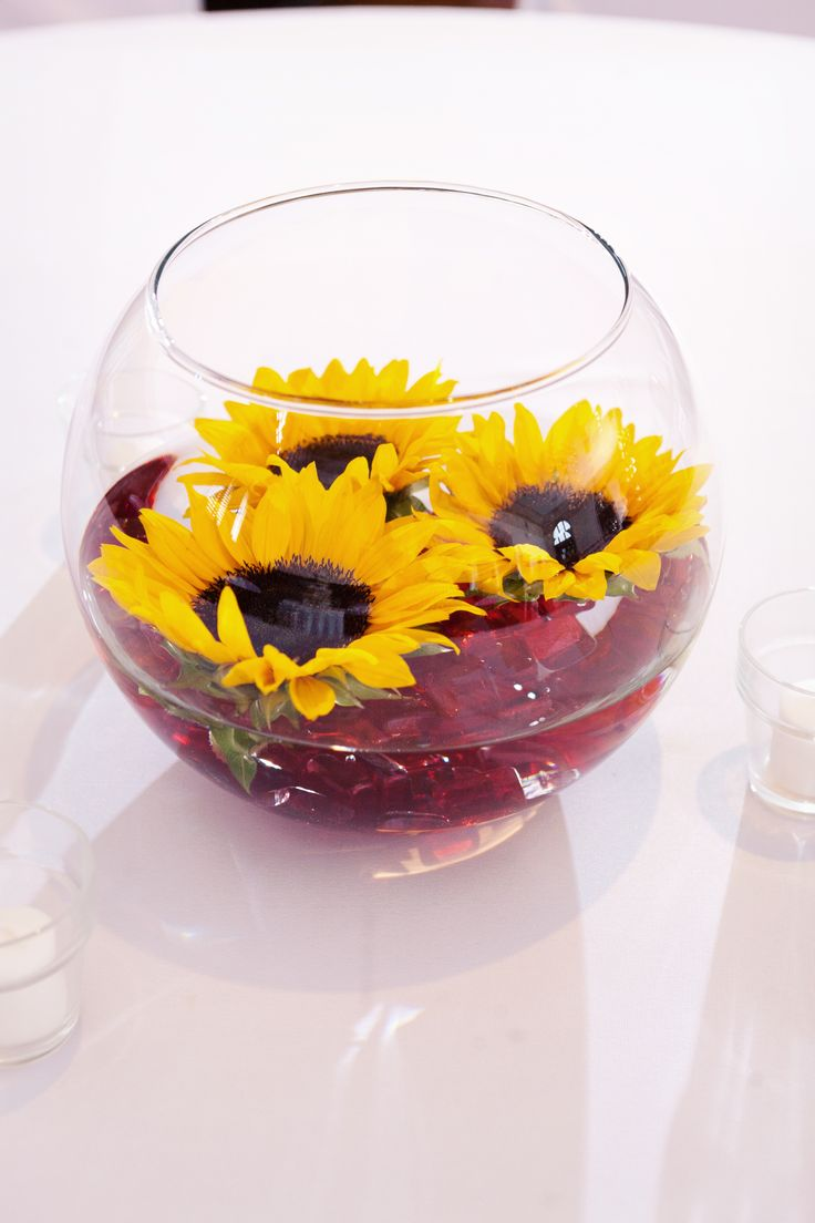 Table centerpieces- floating sunflowers with red pebbles