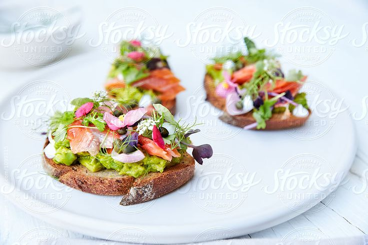 Avocado Toast with smoked salmon caviar, homemade rye bread, crispy capers, pickled pearl onions, and edible flowers