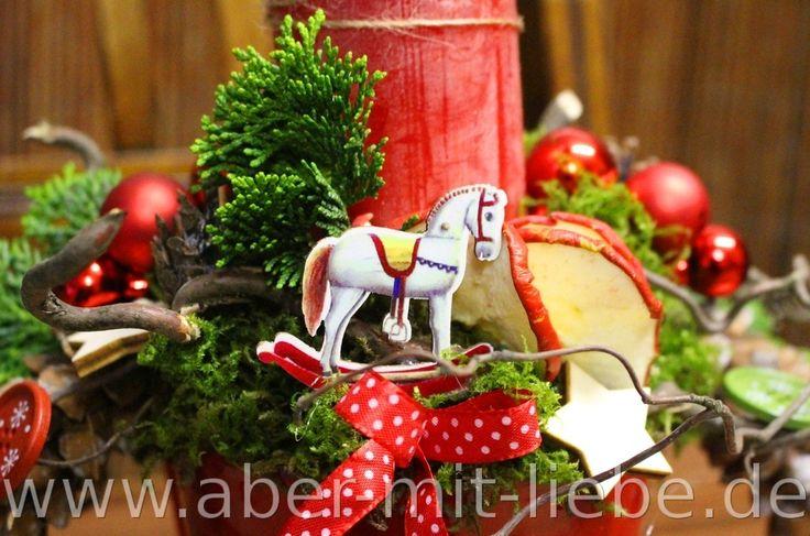 Nostalgische Weihnachtsdeko, Kerzengesteck in rot mit nostalgischer Deko, Weihnachtsnostalgie mit Apfelscheiben, Schaukelpferd, roter Kerze und Schleifchen