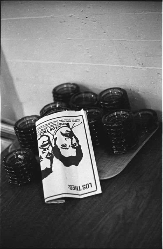 Festival de Flor y Canto, 1973: Films and Photographs - Photograph of a Los Tres pamphlet on a pile of ashtrays at the Festival de Flor y Canto, University of Southern California, Los Angeles, 1973. Los Tres were three drug pushers who, in the early 1970s, emerged as symbols of U.S. oppression to community activism.