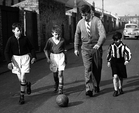 Sir Bobby Charlton playing football with a couple of kids on the streets of Ashington. (1958)