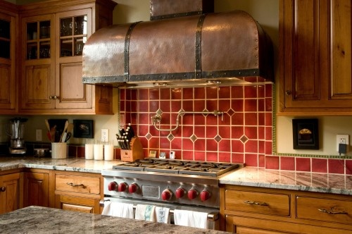 Commercial range and hand hammered hood anchor the kitchen - looks a bit like the top from an old chest