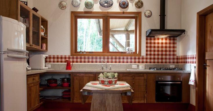 Deste ângulo da cozinha projetada pela arquiteta Suzy Melo, vê-se a bancada de trabalho com tampo de mármore e os armários de madeira. Sobre o frontão da pia, ladrilhos hidráulicos protegem a parede dos respingos de água. A coifa preta remete ao ferro pintado e a mesa em madeira rústica é de abrir. Os armários superiores (com desenho do escritório) são fechados por tela de galinheiro e, sobre a janela de madeira, a coleção de tampas para sopeiras arremata a ambientação