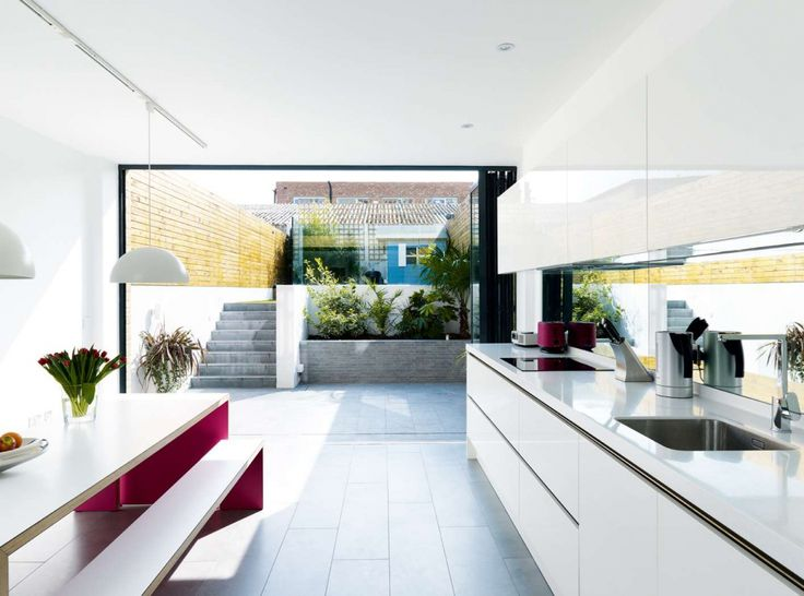 Modern Kitchen In A Semi Basement Extension With Huge Glass Wall And Steps  To The Garden.