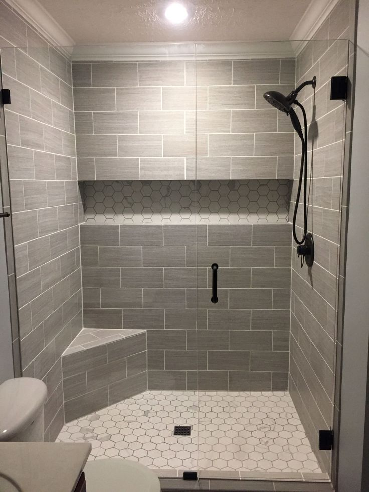 """Our finished walk-in shower.   Walls: Florim USA 6x24 (cut in half) """"Layers"""" tiles in Sediment;  Shower floor & back of the shelf: Florim USA """"Luxury"""" hexagon mosaic tiles in Calacatta;  Glass door/wall: Glass Warehouse 78""""x57.5"""" Frameless Hinged w/ rubbed bronze fixtures;  Shower head: Delta 58480-RB-PK; Shower Valve Trim: Delta T17038-RB Lahara Monitor 17 Series; Drain cover: Ebbe E4407 Square Shower Drain Grate, Rubbed Bronze; Light: Globe Electric 90752 water resistant LED"""