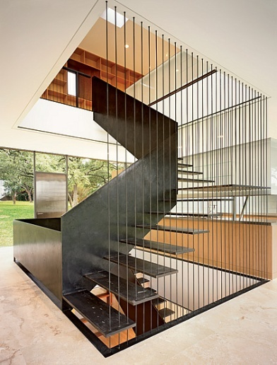 """Sculptural staircase """"made with a ribbon of steel"""" at innovative trilevel house for a young family near Austin, Texas by architect Peter L. Gluck"""