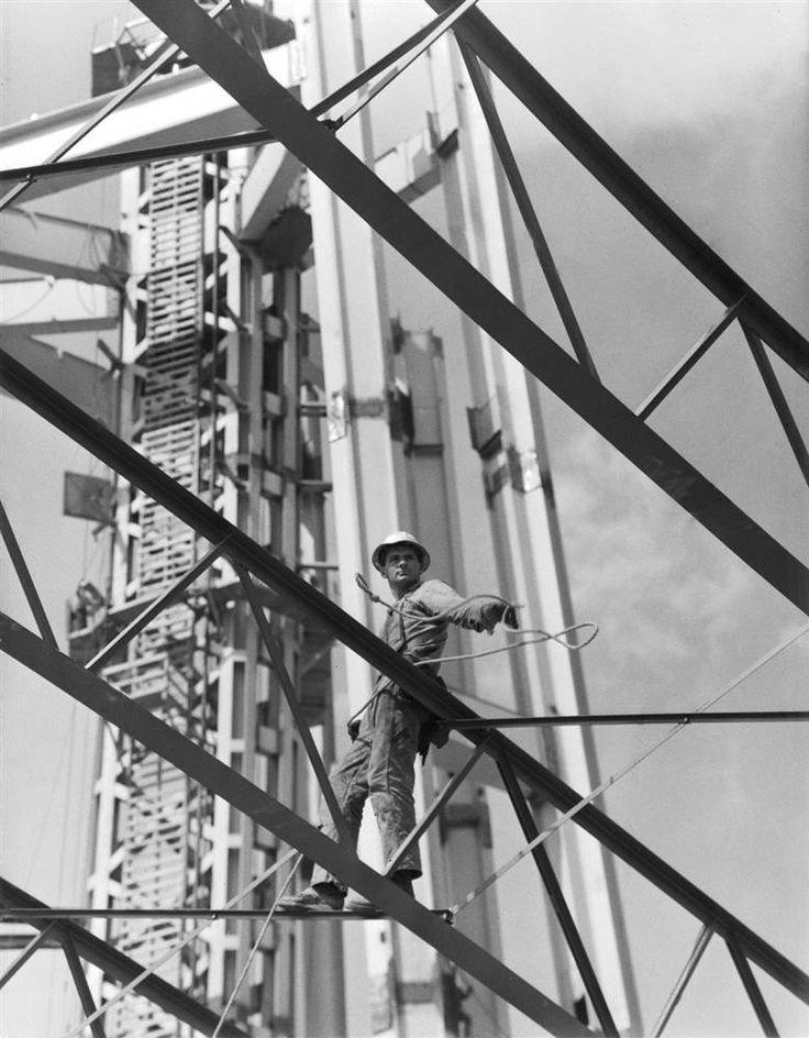 An ironworker throws a line to a buddy during the installation of the upper levels of the Space Needle during construction in 1961.