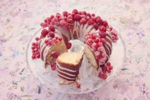 Slice of lemon drizzle bundt cake, decorated with sugared raspberries and redcurrants