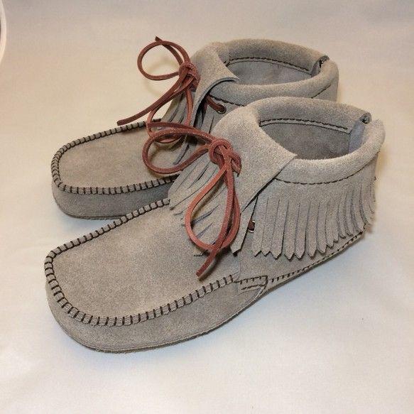 起毛革を使った手縫いのハイカットモカシンです。現行のハイカットモカシン(HMB-GL)をバックファスナー・タイプとして、靴の脱ぎ履きを容易にしました。甲のモカ縫いを外側で摘んで縫っています。普段履きの靴として足指に優しいオブリークトウ形状のつま先としました。中足部から踵部にかけて、ウェッジソールとすることで歩きやすくしました。天然素材を使用しているため、小さなキズや色ムラがある場合があります。ご承知のほど宜しくお願い致します。靴のサイズは、5枚目の写真にある「スティックの長さ」を測ってお知らせいただけると確実です。【サイズ】21.5cm、22.0cm、23.0cm、24.0cm、25.0cm(ウィズ:21.5cmはC、その他はE)【靴の色】グレージュ【靴紐の色】茶【縫糸の色】焦げ茶【ヒール高】1.6cm【素材】牛ベロア革【技法】手縫い、一部ミシン縫い、ハンドメイドその他、お気軽にお問い合わせください。