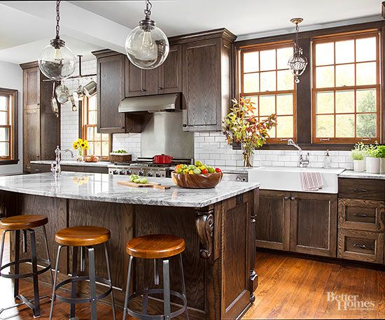 White subway tile and gray-vein granite keep rich dark-stained oak cabinets from weighing down this elegant kitchen.The wood cabinetry is a nod to the home's 1930s roots and creates interesting old-world charm when juxtaposed with lighter hardwood floors and window frames.
