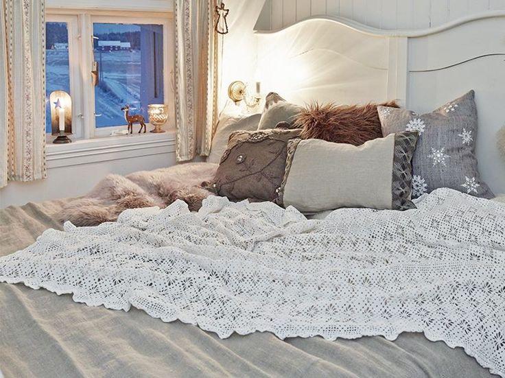 HVIT JUL PÅ BALKE GÅRD: Stemning på soverommet. På soverommet lar Marianne bestemorens blondeduk pynte opp sengeteppet i lin. En samling med puter i herlige jordfarger og en lyslykt i vinduet ut mot jordene gjør det lunt og stemningsfullt | BoligPluss